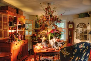 The cozy dining room holds more treasures, including a signature quilt (not seen) from Mark's family, a redware-filled cupboard and a chandelier made by Denver tinsmith Charles Messner. In decorating the room for the holidays, Kerry utilized shades of red and pink for the floral arrangements that top the tables and are nestled in the chandelier. Note the pink-hued ornaments that fill a garden urn.