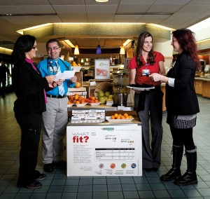 "A display in the hospital's dining area is dedicated to the super foods we read about but rarely get to taste. Samples are shared through the displays that change on a monthly basis, as are recipes and other information. January's super foods display focused on citrus. Here, Brynn Kline (in red) shares samples with Alicia Mulcavage, while Dr. Christian Hermansen, MD, and Yvette Soulidis study the recipe handouts that are made available. ""It's definitely a learning process,"" says Brynn."