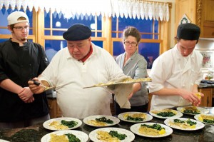 """The Elia family – Salvatore, Nino, Elizabeth and Francesco – worked in tandem to create the dinner that took its inspiration from Nino's native Sicily. Here, they plate the third course: fillet of sole """"oreganata"""" and sautéed spinach."""