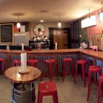 The first floor of Divine Swine features a wood-topped bar and hi-tops crafted from beer kegs.