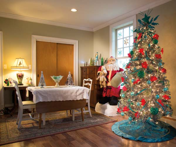 A corner of the main floor of Dawn's Millersville home has a decided vintage theme. Last year, she utilized a red and turquoise color scheme for the space during the holidays. Turquoise/teal was a popular ornament color back in the '60s, so it's right at home in Dawn's interpretation of a vintage holiday. The focal point of the room is an aluminum tree whose needles are silver and black in color. Her collection of miniature trees tops the dining table and chest. Because Dawn is so late in putting up her tree, she keeps it in place through Valentine's. Her snowman collection and the snowflakes on the window panes add to the post-holiday winter theme.