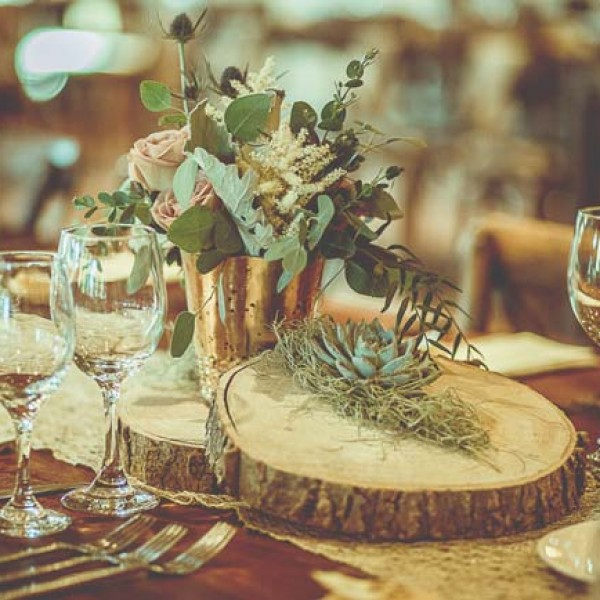 Bouquets and centerpieces provided the organic element for the wedding. Blocks of wood were topped with vases that held greenery and florals such as astilbe and garden roses.