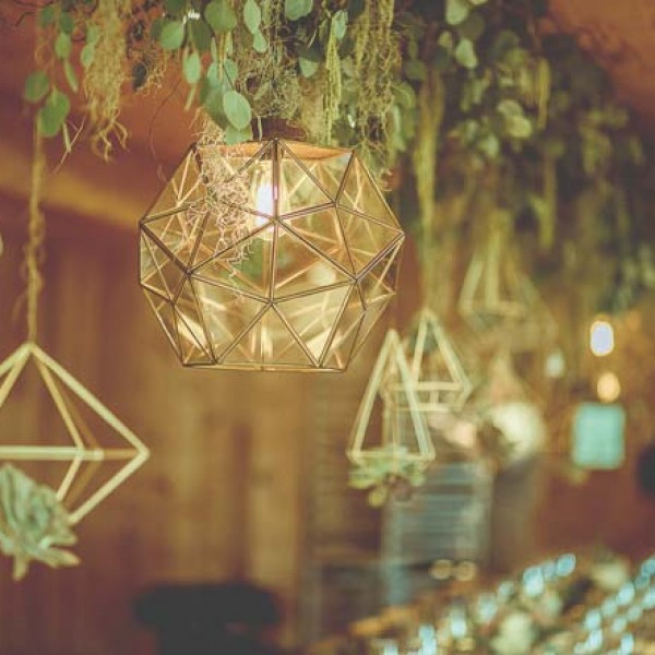 Branches embellished with greenery and moss were suspended from the ceiling of the reception venue. Nordic-inspired, geometric-shaped accent pieces and lighting fixtures hung from the branches. The hanging accent pieces were subtly embellished with succulents.