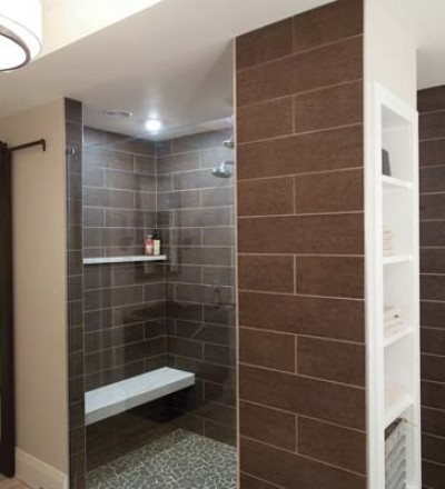 The bronze tile that comprises the walk-in shower has a wood-like texture. The tower provides added storage for towels. Note the custom glass/wood sliding door that provides access to the water closet.