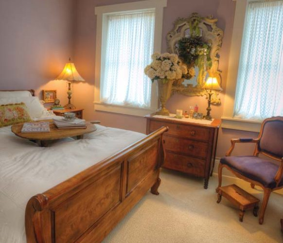 Antiques and an amethyst wall color provide for a comfy guest bedroom.