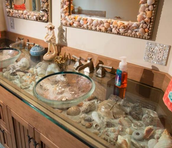 Jim Schopf, Andrea's husband, designed the double vanity. The board over the cabinet doors flips down, allowing Andrea to switch shells in and out of the sand-covered shelf. Andrea created the shell-embellished mirrors.