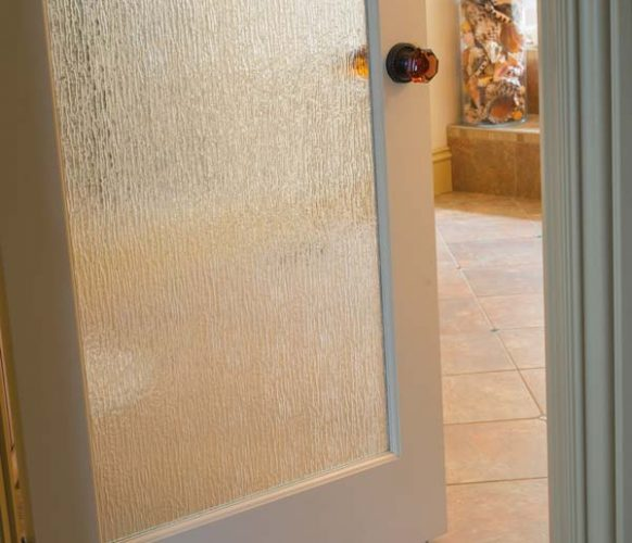 The glass door that provides access to the master bath mimics rain water.