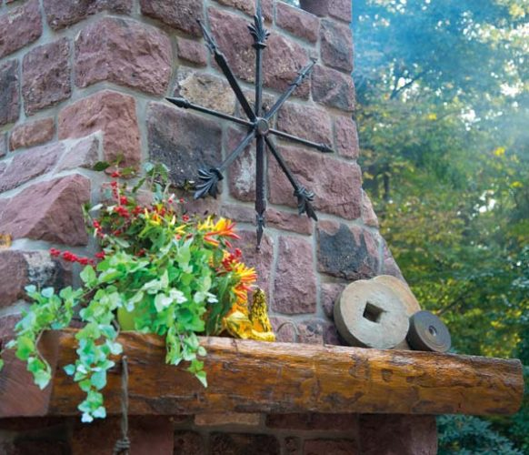 The mantel (also taken from the farm) is decorated with millstones and a metal sculpture that was created from pieces of an old iron fence.