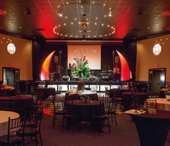 As a nod to Dave's career as special events manager for the Chicago Bulls, the stage was flanked with huge, inflatable red horns. The Hamilton Ballroom's neutral walls were enlivened by uplights, washing the room in vibrant red. Bold arrangements of tropical flowers completed the decor.