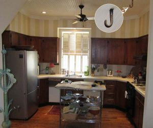 The kitchen had been remodeled in the '60s. The cabinetry not only darkened the room, but the upper cabinets were out of scale, making the space seem very bottom heavy. Note the infamous hook in the ceiling, which dates to the early days of the 20th century, when the building housed a sleigh and later, cars.