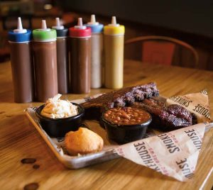 House-made rubs and a selection of sauces allow guests to experiment with the taste and heat factor for barbecue, ribs and brisket. Here, sides include baked beans, a cornbread muffin and cole slaw.