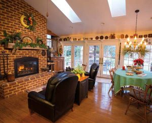 A fireplace is the focal point of the great room. Skylights and a wall of French doors admit plenty of natural light and provide a scenic view of the wooded property. The shelving over the doors holds Elaine's collection of antique crockery. A quilt covers the dining table.