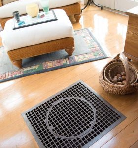 """""""The sitting room is cozy when it snows,"""" she adds. The iron grate is one of Elaine's finds, plus it is functional, as warm air from the lower level filters through it and heats the room."""