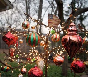Ornaments and lights hang from an iron tree that sits outside the screened porch.