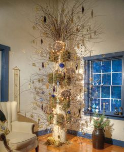"""When Elaine bought four architectural columns that were removed from the Abraham Lincoln Hotel in Reading, she envisioned using one as a """"tree"""" on which she could display the ornaments and other keepsakes she had collected on her travels. Floral designer Kerry Kegerise devised a way to attach branches to the tree. Initially, Elaine decorated it with seasonal items, but decided she liked her Christmas ornaments the most, so the theme remains in place on a year-round basis."""