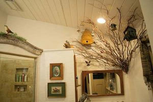 """Elaine refers to the master bath as """"the bird bath,"""" due to its bird-related décor. Kerry Kegerise helped her design the """"tree"""" that grows out of one of the walls. Birds and birdhouses decorate it. She found the wooden arch that tops the shower door at a """"junk place"""" along Route 322 and put it to use."""